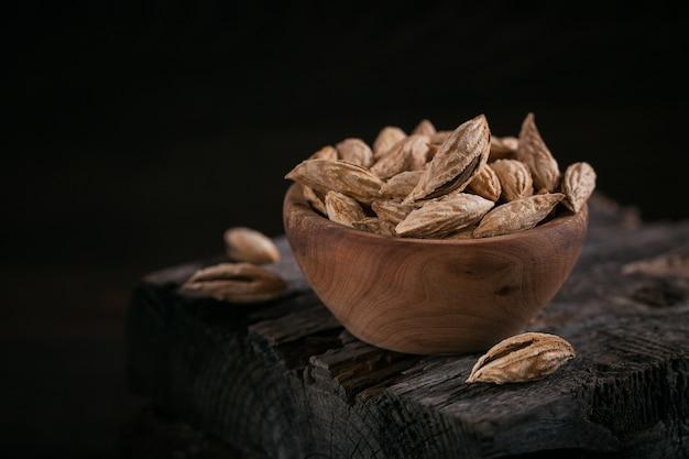 Stapel amandelnoten in een kom op een donkere houten ondergrond. verse noten in hun schelpen.