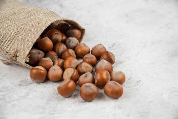 Stapel biologische gepelde hazelnoten in jute op marmeren tafel.