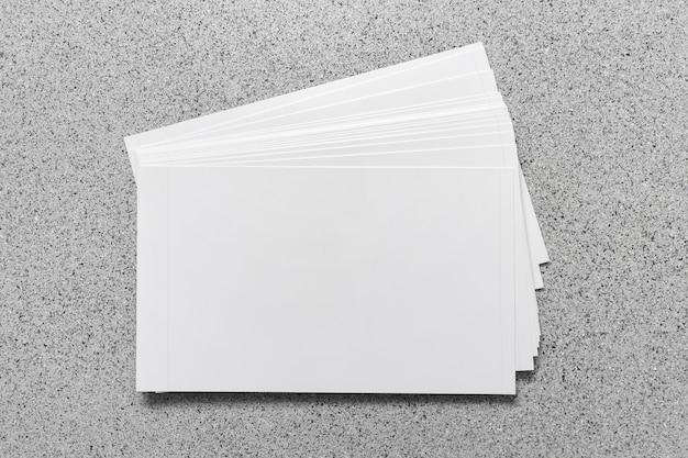Stapel blanco kaarten sjabloon mockup op grijs gestippeld oppervlak.