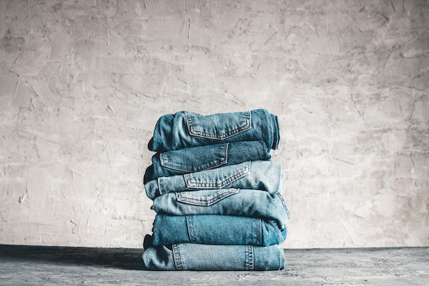 Stapel blauwe spijkerbroek op een grijze achtergrond