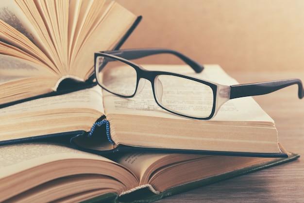Stapel boeken en brillen erop op houten tafel, close-up