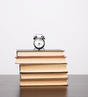Stapel boeken en een zwarte wekker op de tafel