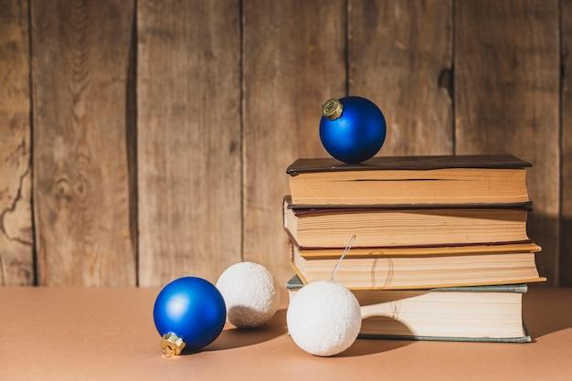 Stapel boeken en kerstboomversieringen op houten ondergrond.