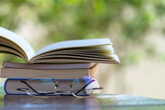 Stapel boeken en leesbril op tafel, met wazig groene achtergrond.