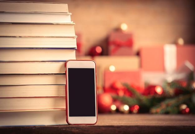 Stapel boeken en mobiele telefoon met kerstcadeaus op achtergrond