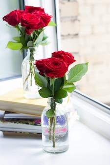 Stapel boeken en rozen in vazen in de buurt van een open raam