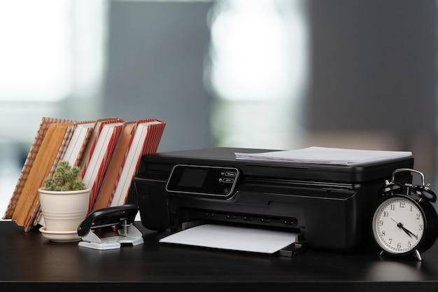 Stapel boeken en thuisprinter tegen onscherpe achtergrond