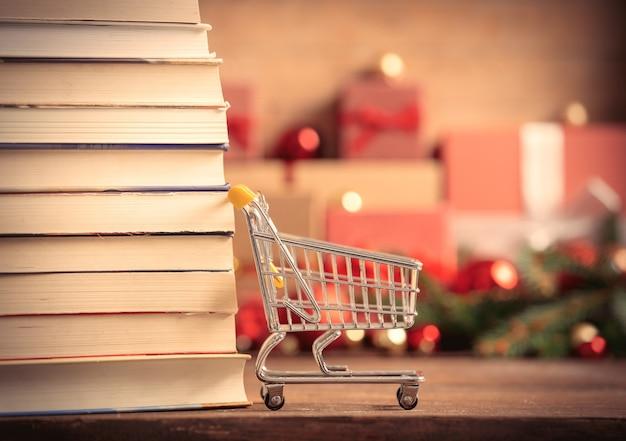 Stapel boeken en winkelwagentje met kerstcadeaus op achtergrond