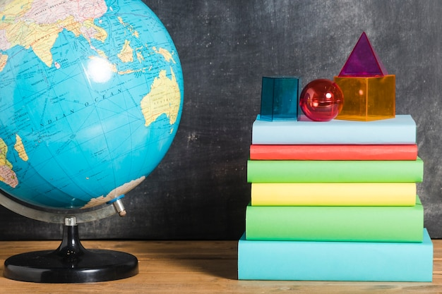 Stapel boeken in de buurt van earth globe