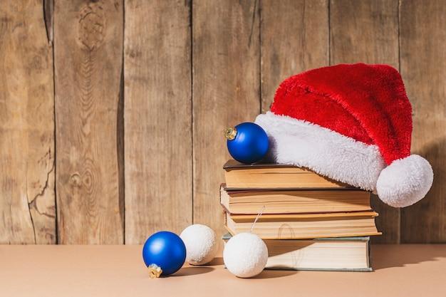 Stapel boeken, kerstboomversieringen en kerstmanhoed op houten ondergrond.
