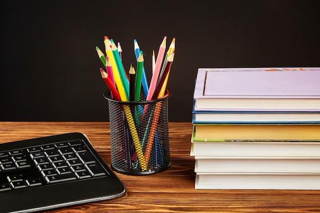 Stapel boeken, kleurpotloden, toetsenbord.