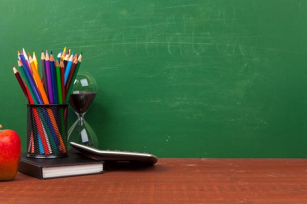 Stapel boeken met appel en potlood op tafel