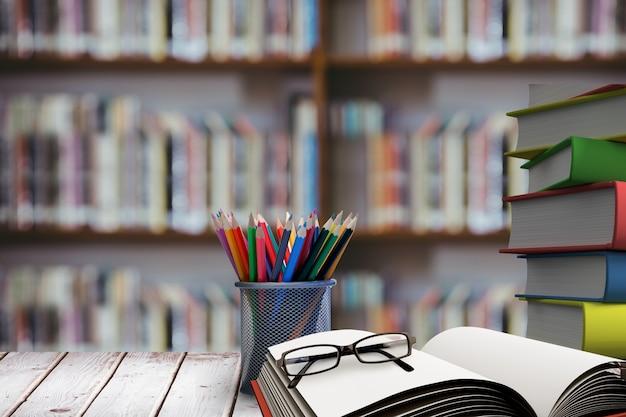 Stapel boeken met een bril op houten bureau