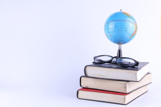 Stapel boeken met globe en glazen geïsoleerd op een witte achtergrond