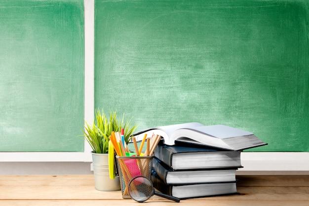 Stapel boeken met ingemaakte plant en potloden in mand container met vergrootglas op de houten tafel