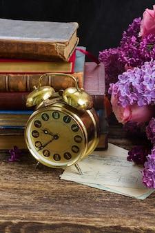 Stapel boeken met klok en bloemen