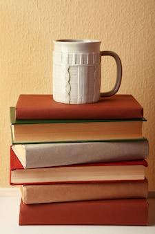 Stapel boeken met kop warme drank op tafelblad op lichte muur