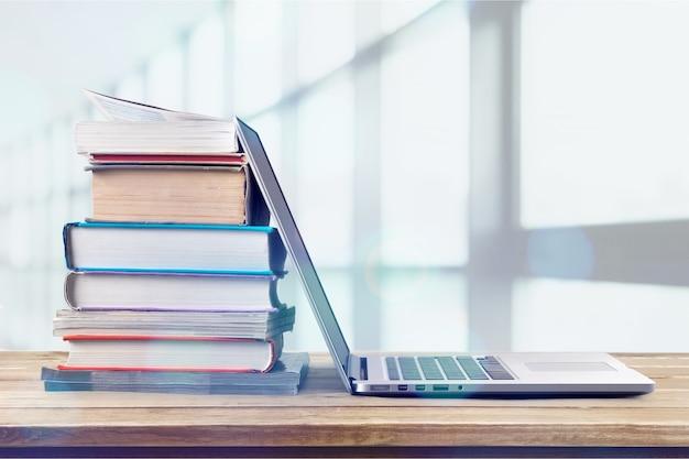 Stapel boeken met laptop op houten tafel