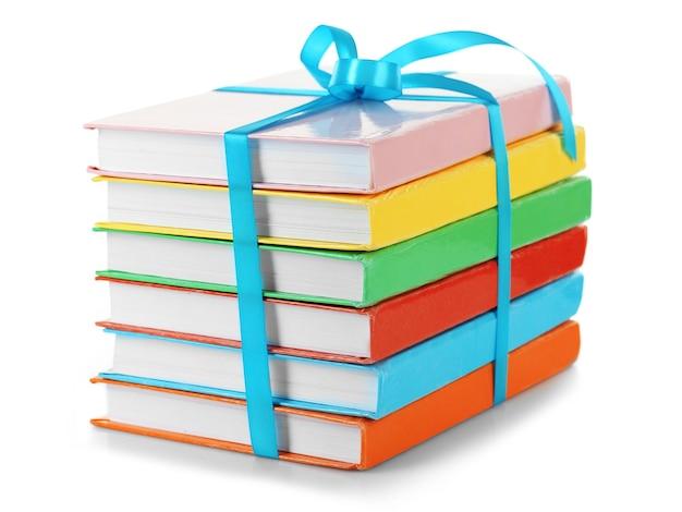 Stapel boeken met lint op wit wordt geïsoleerd
