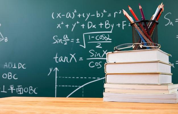 Stapel boeken met potloodhouder en glazen tegen een schoolbord