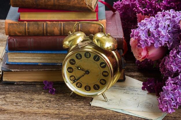 Stapel boeken met wekker en bloemen