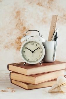 Stapel boeken met wekker. tijd voor lezen, concentratie in studie, huiswerk of onderwijsconcept.