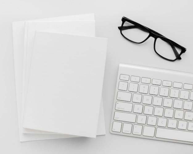 Stapel boeken op bureau naast bril