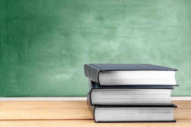 Stapel boeken op houten tafel met schoolbord