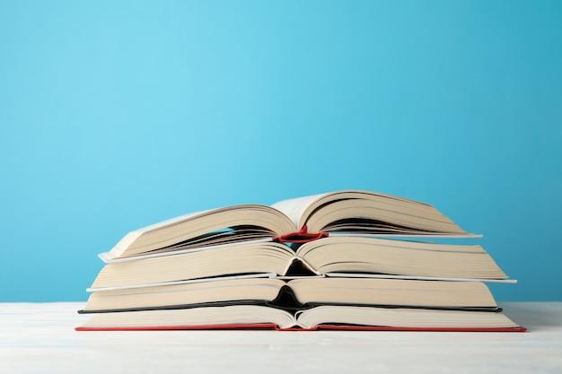 Stapel boeken tegen blauwe achtergrond, ruimte voor tekst