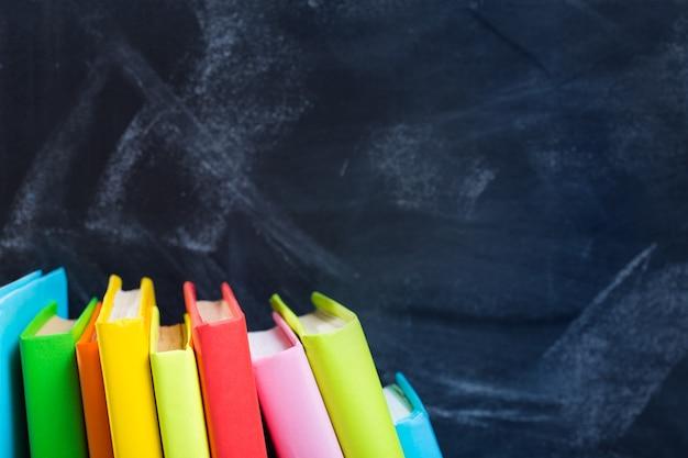Stapel boeken tegen de achtergrond van het lerarenbord