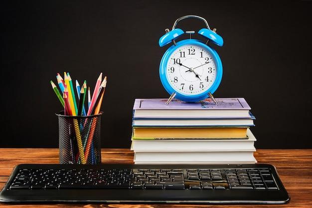 Stapel boeken, wekker, kleurpotloden, toetsenbord.