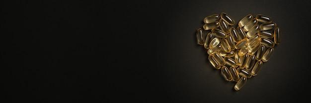 Stapel capsules omega 3 op zwarte achtergrond. hartvormige visoliepillen. close-up, bovenaanzicht, product met hoge resolutie.