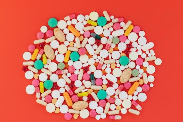 Stapel capsules, pillen op een rode achtergrond