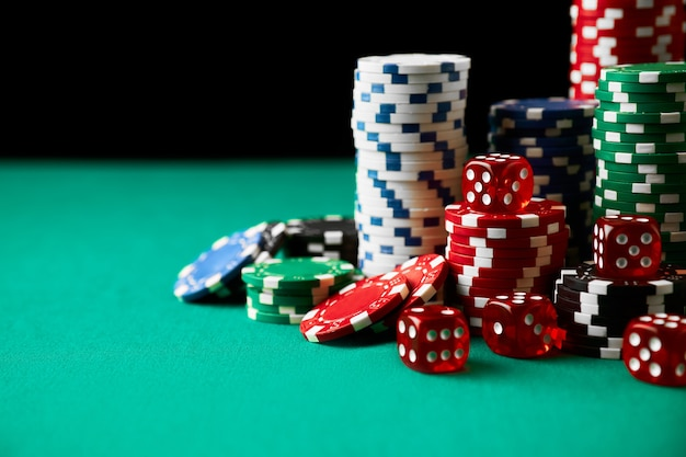 Stapel casino speelpenningen en dobbelstenen op groene tafel