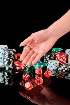 Stapel casino speelpenningen en rode dobbelstenen geïsoleerd op reflecterende zwarte achtergrond