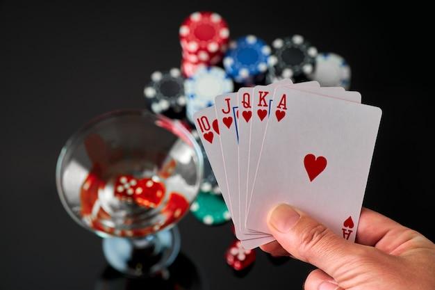 Stapel casino speelpenningen glas martini vermout en rode dobbelstenen geïsoleerd op reflecterende zwarte ...
