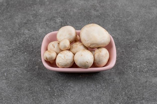 Stapel champignons in roze kom over grijs oppervlak