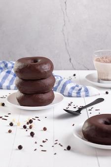 Stapel chocolade donuts op lichte achtergrond. verticaal formaat.