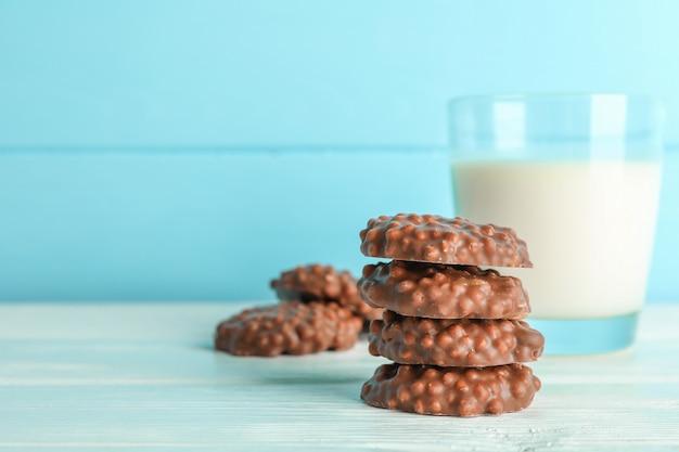 Stapel chocoladekoekjes met glas melk op witte lijst tegen kleurenachtergrond