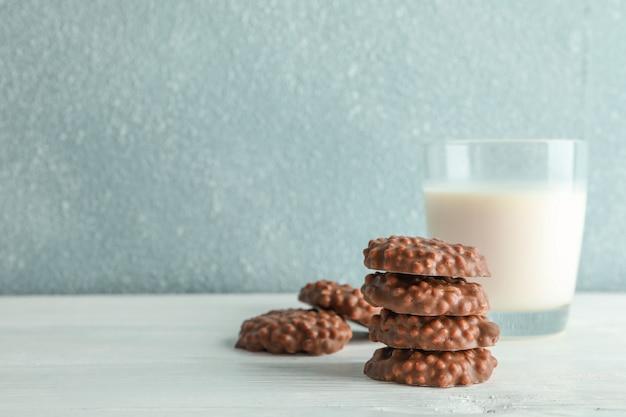 Stapel chocoladekoekjes met glas melk op witte lijst tegen lichte achtergrond