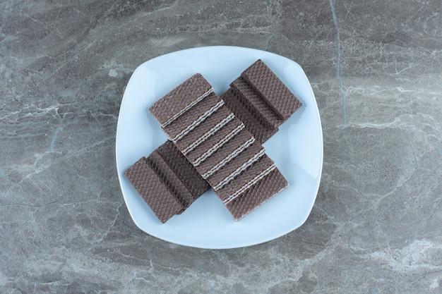 Stapel chocoladewafels op witte keramische plaat.