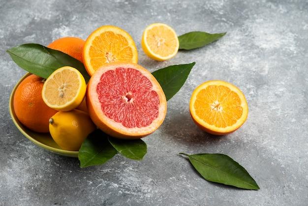 Stapel citrusvruchten in kom over grijze tafel.