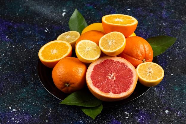 Stapel citrusvruchten op zwarte keramische plaat.
