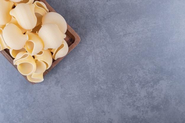 Stapel conchiglie pasta op een houten bord.