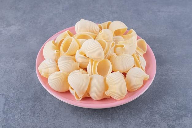 Stapel conchiglie pasta op roze plaat.