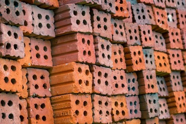 Stapel de rode bakstenen die op de achtergrond zijn gerangschikt voor de bouw