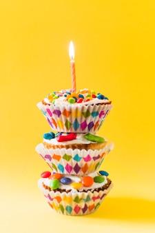 Stapel decoratieve cup cakes met brandende kaars op gele achtergrond