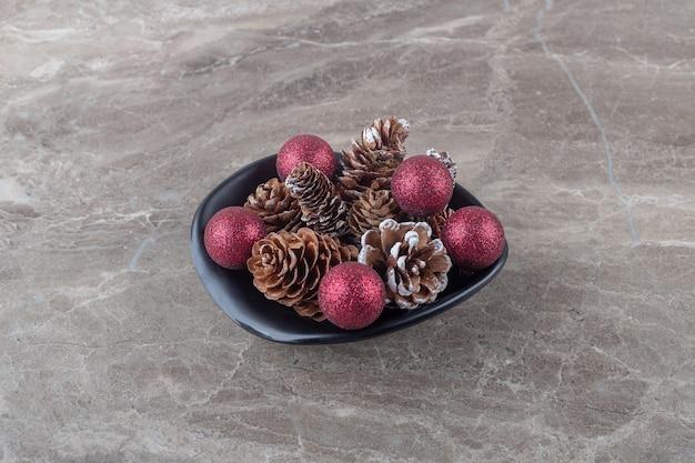 Stapel dennenappels en kerstballen in een kom op marmeren oppervlak