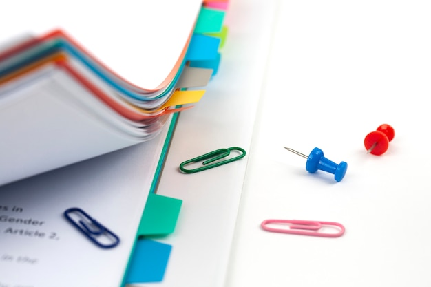Stapel documenten met kleurrijke clips op wit
