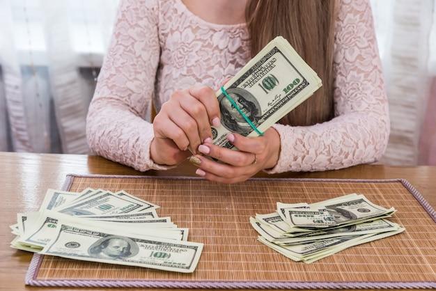 Stapel dollar biljetten in handen van de vrouw